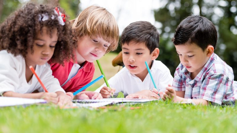 Group of school kids coloring outdoors looking happy