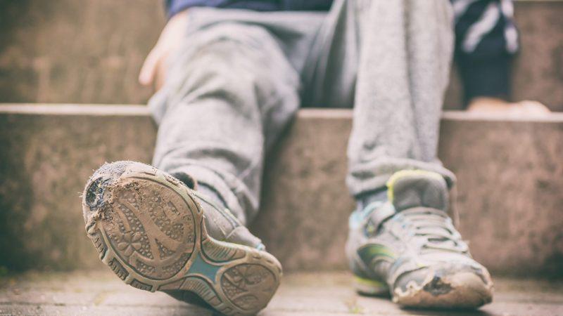 Alte kaputte Schuhe eines kleinen Jungen als Symbol für Kinderarmut