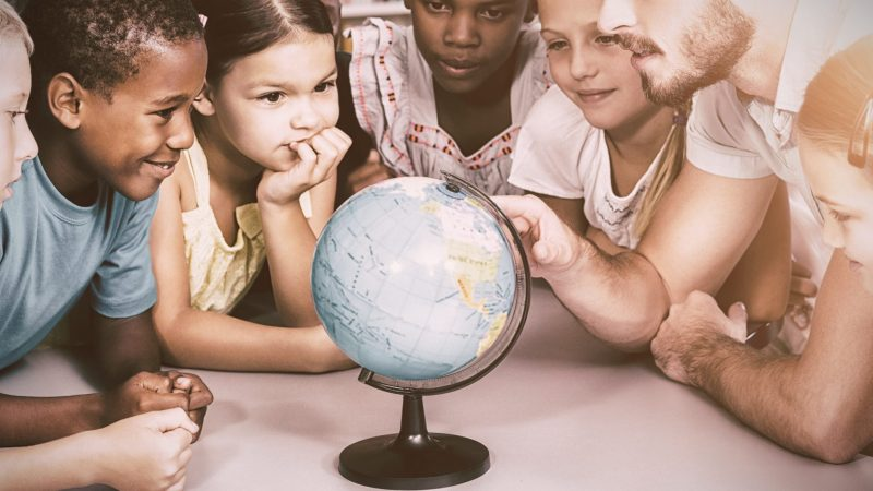 Students and teacher looking at globe in library